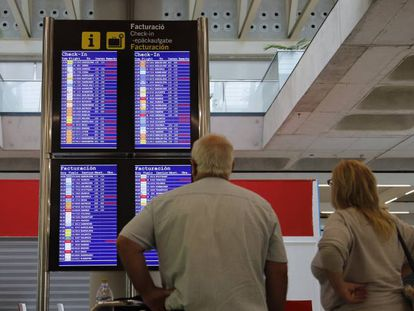 Pasajeros consultando vuelos en el aeropuerto de Palma de Mallorca.