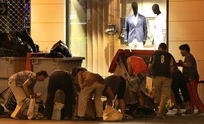 Un grupo de personas buscan en bolsas de basura alimentos a las puertas de un centro comercial  en la calle Alberto Aguilera, en Madrid