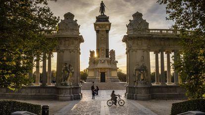 Una chica disfruta de un agradable paseo en bicicleta al atardecer antes de volver a casa en el parque del Retiro.