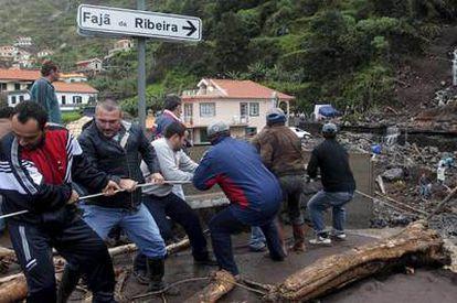 Un grupo de hombres trata de retirar un tronco de un arroyo en Ribeira Brava (Madeira).