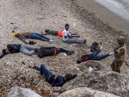 Un soldado custodia a varios jóvenes inmigrantes, algunos de ellos heridos, en la playa del Tarajal, en la frontera de Ceuta.