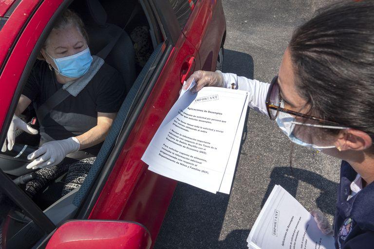 Una representante del ayundatimiento de Hialeah, Florida, reparte documentos para solicitar los beneficios por desempleo.