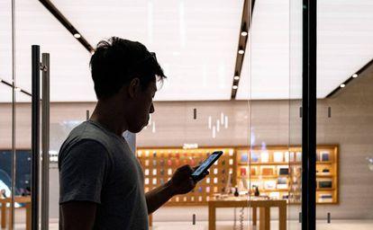 Un hombre revisa su teléfono frente a una tienda de Apple en Singapur