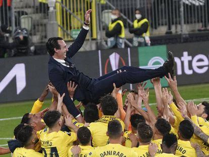 Los jugadores del Villarreal mantenan al entreandor, Unai Emery, tras proclamarse con el título.