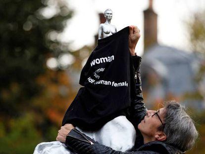 En la imagen, una activista viste con una camiseta la escultura en señal de protesta. En el vídeo, la escultura en su entorno, un parque de Londres.