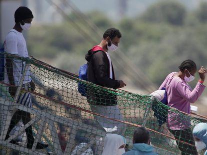 Migrantes desembarcando del  'Geo Barents' en el puerto siciliano de Augusta antes de pasar al barco de cuarentena 'Aurelia'.