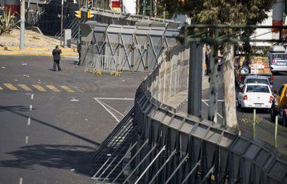 Un hombre camina junto a las vallas que han sido colocadas para resguardar el Congreso mexicano en vísperas de la investidura de Enrique Peña Nieto.