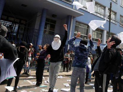 Manifestantes tiran papeles al aire durante una protesta en una universidad en Valparaiso.