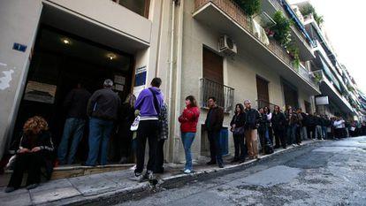 Desemplados hacen cola en una oficina del Servicio Nacional de Empleo para recoger cheques de ayuda, en Atenas.