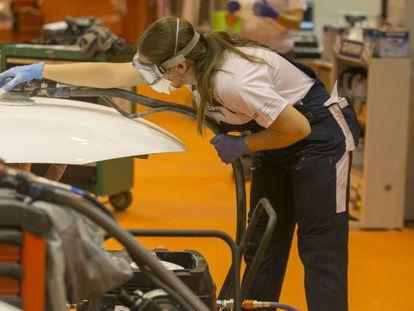 Un estudiante de Formación Profesional pinta un vehículo.