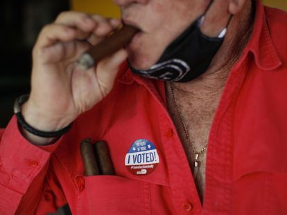 """Un hombre fuma un habano mientras porta una pegatina que dice """"¡yo voté!"""", esta semana en Miami."""