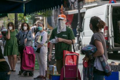 Un grupo de personas espera su turno en el mercado municipal de San Antón, en Madrid, este sábado.