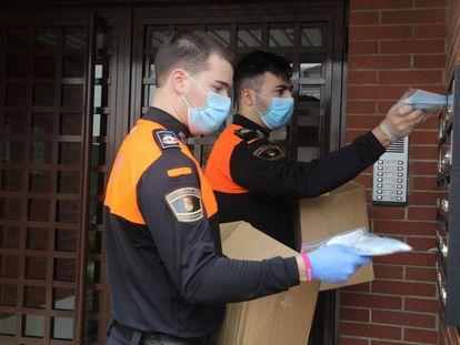 Dos voluntarios de Protección Civil, durante el reparto de mascarillas este jueves en Torrejón de Ardoz, Madrid.