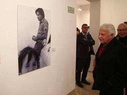 El experesidente Felipe González observa una de sus fotografías de la exposición de Pablo Juliá en Sevilla (detrás).