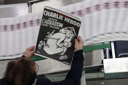 Un empleado de una imprenta sostiene una copia de la última edición del semanario francés 'Charlie Hebdo'.