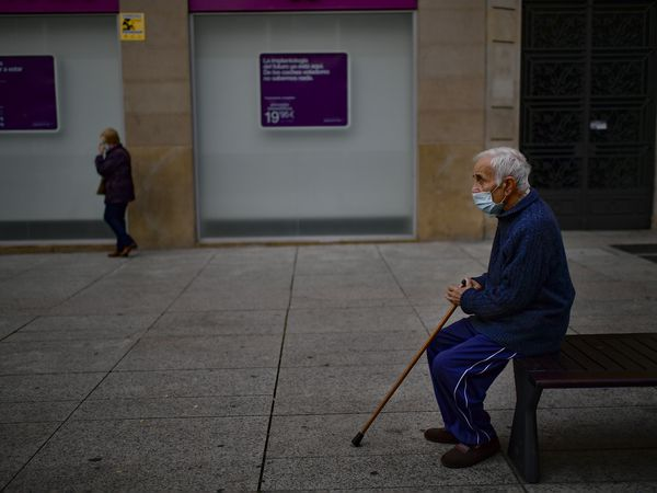 An elderly man sits on a bench wearing a face mask to protect against coronavirus, in Pamplona, northern Spain, Saturday, Oct. 17, 2020. (AP Photo/Alvaro Barrientos)