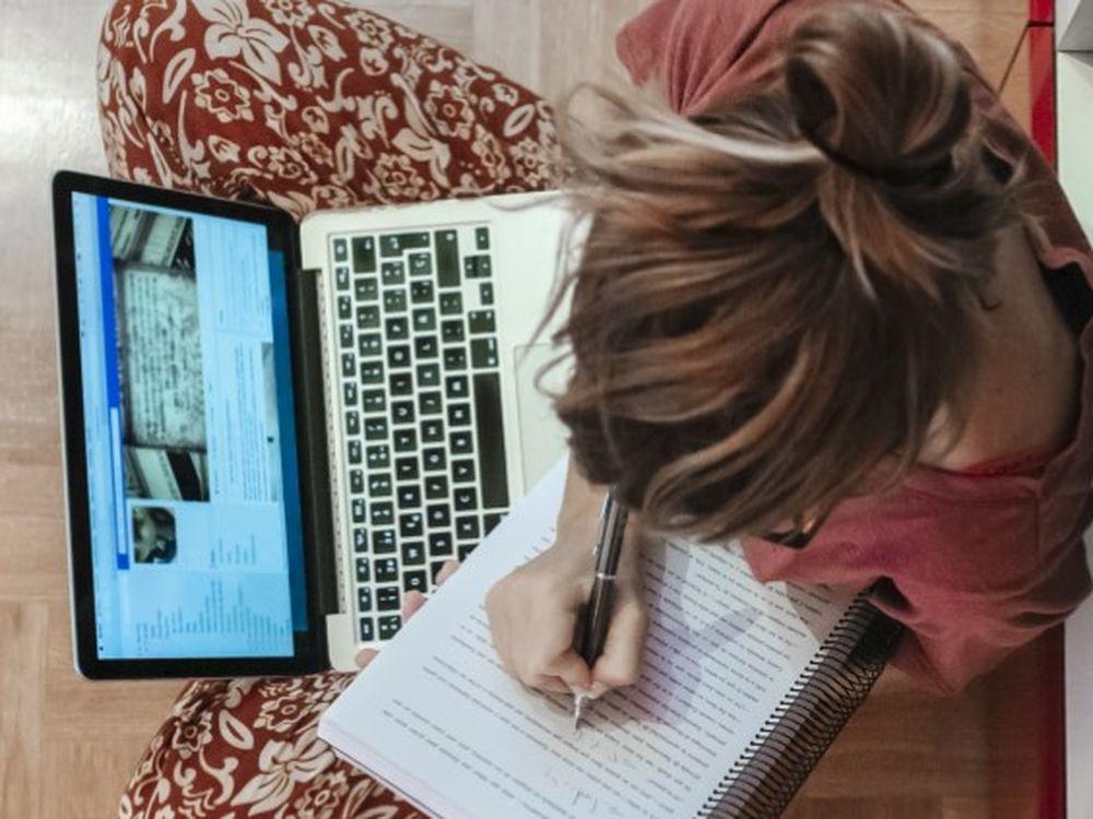 Una joven escribe a mano mientras consulta su ordenador.