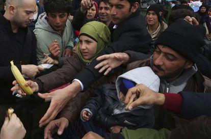 Migrantes reciben alimentos este martes en el puerto de El Pireo (Grecia).