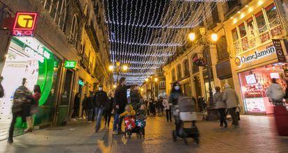 Varios viandantes, en la calle Alfonso I de Zaragoza, adornada con el alumbrado navideño.