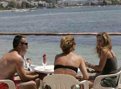 Tres turistas, en una terraza de la playa de Talamanca (Ibiza).
