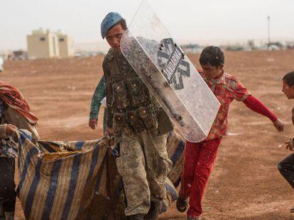 Un soldado turco, junto a refugiados sirios en Sanliurfa (Turquía), el 2 de octubre