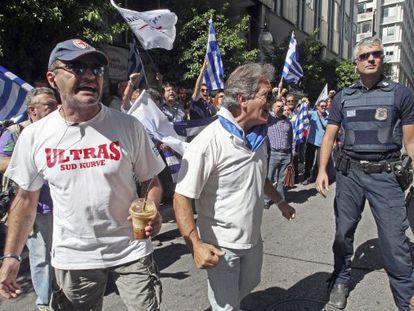 Griegos se manifiestan mientras esperan a los representantes de la troika frente al ministerio griego de Finanzas en Atenas.