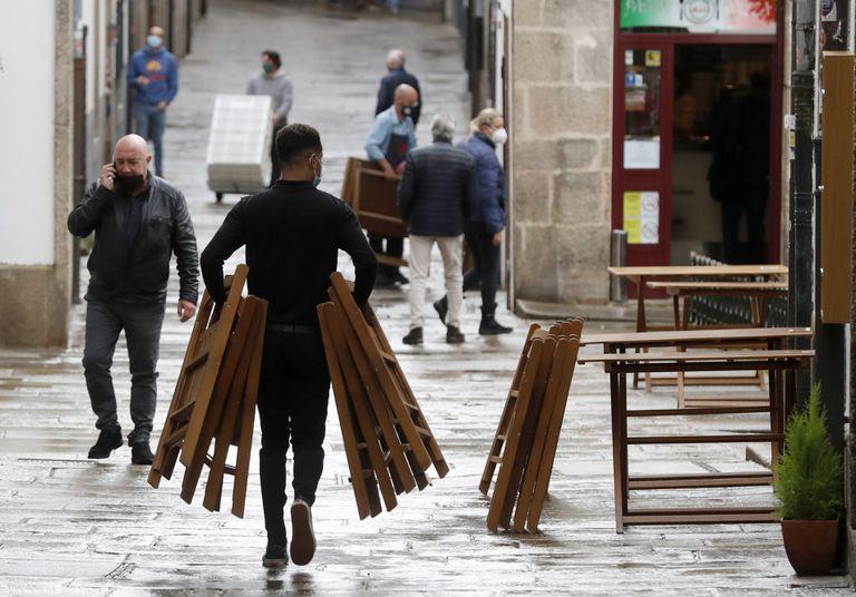 Un camarero monta una terraza en una calle de Santiago a finales de octubre de 2020.