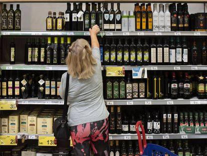 Una clienta de un supermercado español elige una botella de aceite de oliva.
