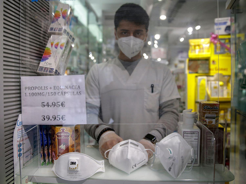 Un empleado muestra distintos tipos de mascarillas en una farmacia en Madrid.