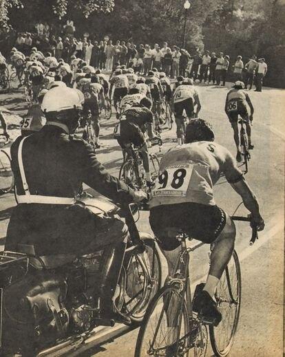 José Pérez Francés, acompañado de un policía motorizado, deja pasar al pelotón, al que aventajaba en una vuelta, en Montjuic.