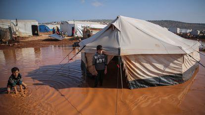 Dos niños sirios son fotografiados junto a su casa, una tienda de campaña, ahora inundada debido a las inundaciones a causa de las fuertes lluvias que cayeron sobre el campo de refugiados de Ma'arrat al-Nu'man, en Siria, el 17 de diciembre de 2020.