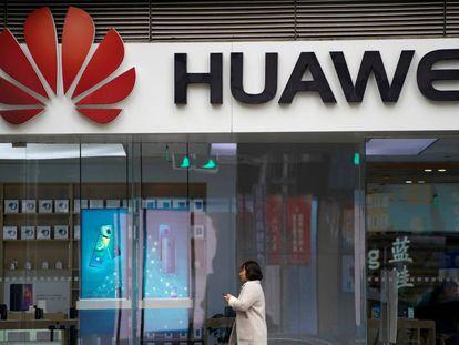 Una mujer camino frente a una tienda de Huawei en Shánghai.