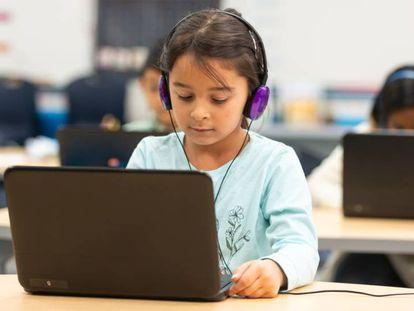 Un grupo de niños usa recursos informáticos en clase.