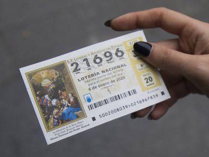 Una mujer muestra su numero de boleto de la lotería del Niño.