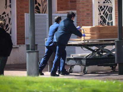 Dos trabajadores trasladan un féretro en el cementerio de La Almudena, en Madrid, el pasado marzo.