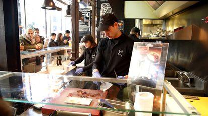 Dos camareros en un puesto del Mercado de San Miguel, en Madrid.