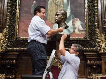 Dos funcionarios retiran el busto de Juan Carlos I del Ayuntamiento de Barcelona el 23 de julio de 2015.