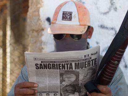 Un hombre del municipio de Ayutla (Guerrero), que combate al crimen organizado lee los sucesos en el periódico.