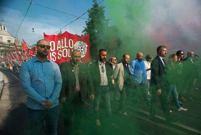 Simone Di Stefano, con traje y corbata, encabeza una manifestación de CasaPound antiinmigración.