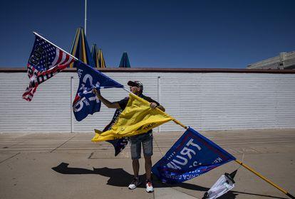 Kelly Johnson, con sus banderas a las afueras del edificio donde cuentan los votos.