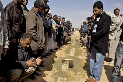 Familiares de las víctimas de los ataques aéreos del régimen sobre Brega rezan durante el funeral, celebrado ayer en Ajdabiya.