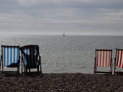 Una mujer toma el sol en una tumbona junto al mar en un día soleado en la playa de Brighton (Reino Unido).
