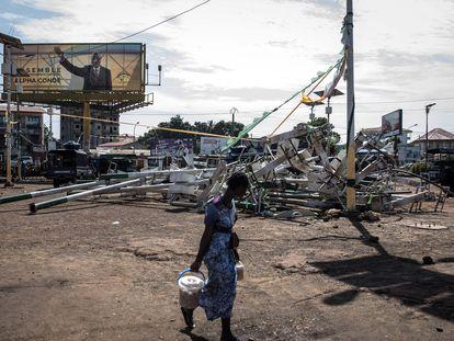 Una mujer camina frente a unas farolas rotas en Conakry durante los incidentes de los últimos días bajo un cartel electoral de Alpha Condé, el pasado 23 de octubre.