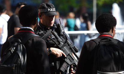 Un policía armado frente a unos estudiantes en una calle de Mánchester, este jueves.
