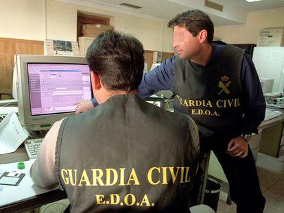 Dos agentes de la Guardia Civil rastrean delitos informáticos cometidos a través de Internet.