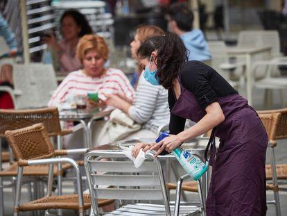 Una trabajadora desinfecta las mesas y sillas de una terraza en la plaza del Castillo de Pamplona.