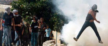 Un palestino devuelve un bote de humo lanzado por el Ejército en una protesta contra la ocupación de terrenos cerca de Nablus, en Cisjordania.