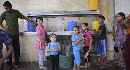 Niños palestinos hacen cola para rellenar botellas de agua en Rafah.