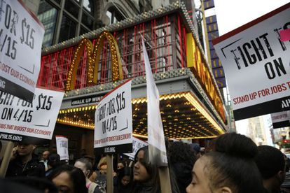 Trabajadores de McDonald's reclaman sueldos más altos frente a un restaurante de la cadena en Nueva York.