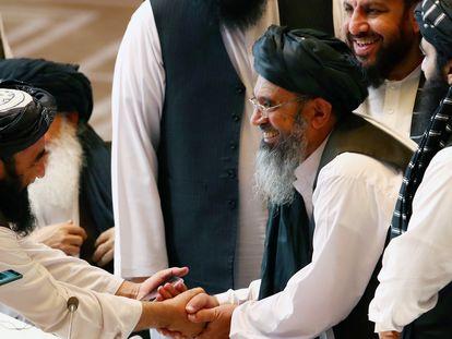 Delegados talibanes se dan la mano durante las conversaciones entre el Gobierno afgano y los insurgentes talibanes en Doha (Qatar) el 12 de septiembre de 2020.